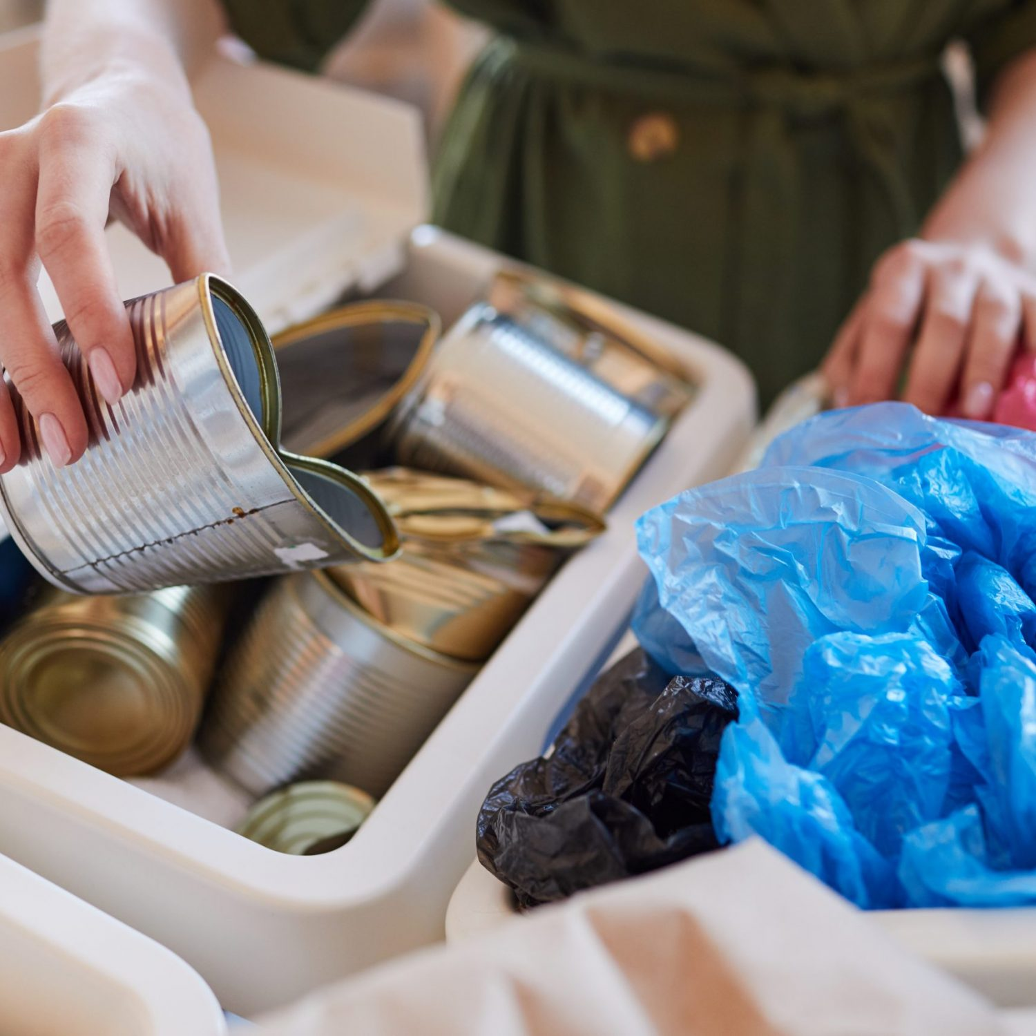 Close,Up,Of,Unrecognizable,Woman,Putting,Discarded,Metal,Cans,Into